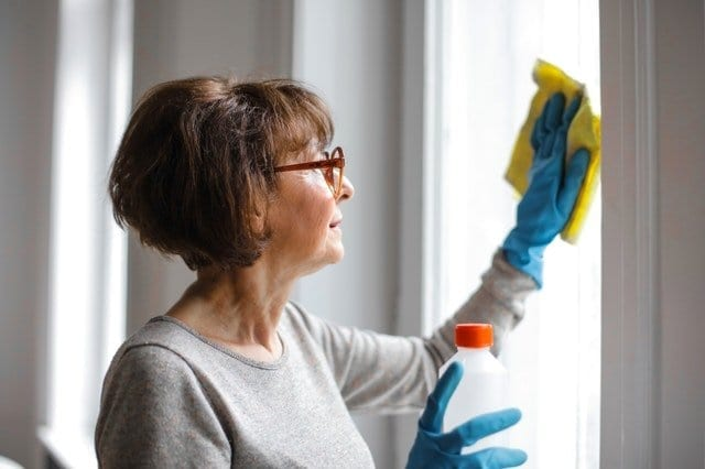 woman cleaning windows during lockdown